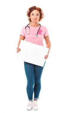 mature woman with stethoscope holding blank banner and looking at camera isolated on white, breast cancer awareness concept