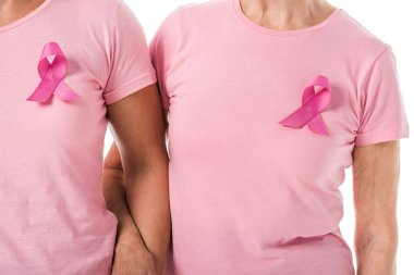 cropped shot of women with pink ribbons holding hands isolated on white, breast cancer awareness concept