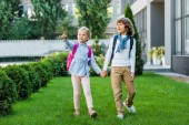 Fotografie niedliche kleine Schüler mit Rucksäcken Händchenhalten und wegschauen während des Gehens auf grünen Rasen