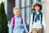 roztomilý nedospělý školáci s batohy, drželi se za ruce a společně chodit