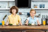 Fotografie entzückende Kinder essen Gemüse und lächelt in die Kamera in Küche