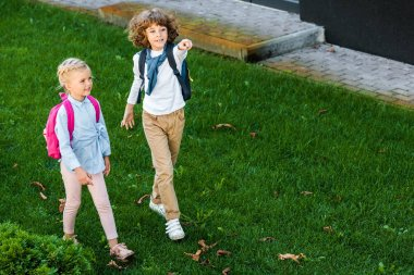 high angle view of cute schoolchildren with backpacks walking on green lawn and pointing away with finger
