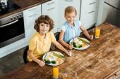 vysoký úhel pohled roztomilé šťastné děti jíst zdravou zeleninu a usmívá se na kameru