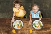 Fotografie vysoký úhel pohled roztomilé šťastných dětí drží vidlice s brokolicí a usmívá se na kameru