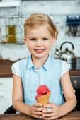 roztomilý šťastné dítě drží lahodné sladké zmrzliny a usmívá se na kameru