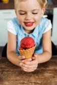 Detailní pohled roztomilé usměvavé dítě drží lahodné zmrzliny