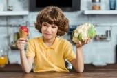 Fotografie nešťastné dítě drží sladké zmrzliny a zdravé květák