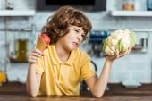 Fotografia bambino infelice che tiene cavolfiore sano e delizioso gelato dolce