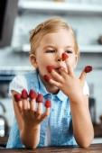 Photo cute happy kid sitting at table and eating ripe fresh raspberries