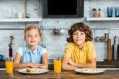 roztomilý šťastných dětí se usmívá na fotoaparátu zatímco sedí u stolu s brýlemi šťávy a chutné sendviče