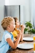 boční pohled roztomilé malé děti jíst chutné sendviče