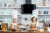 Fotografie rozkošné děti v chef klobouky a zástěry dávat vysoké pět a usmívá se na kameru při společné vaření v kuchyni