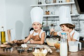 Fotografie cute little kids in aprons and chef hats preparing dough for cookies and smiling at camera