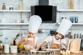 Fotografie niedliche kleine Kinder in Schürzen und Koch Hut Zubereitung Teig für Kekse zusammen