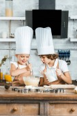 Fotografie cute smiling children in aprons and chef hats preparing dough for tasty cookies together