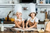 Fotografie entzückende Kinder in Schürzen und kochmützen zusammen leckere Kekse Teig vorbereiten