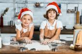Fotografie niedliche glückliche Kinder in Santa Hüte vorbereiten Weihnachtsplätzchen und lächelt in die Kamera