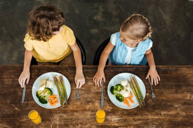 high angle view of adorable kids eating healthy vegetables and looking at each other