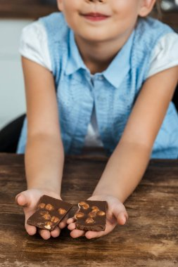 close-up partial view of smiling child holding pieces of sweet chocolate with hazelnuts