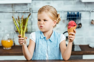 unhappy child holding delicious ice cream cone and healthy asparagus