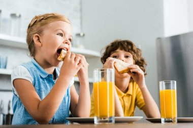 low angle view of cute little kids eating tasty sandwiches