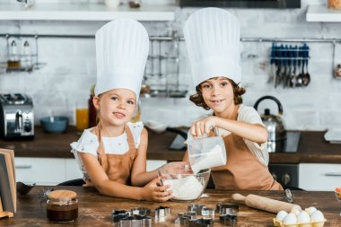 cute little children in chef hats preparing dough for cookies and smiling at camera