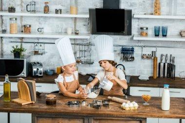 adorable little children in chef hats preparing dough for cookies in kitchen