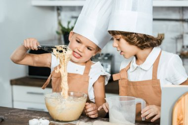 cute little children in aprons and chef hats preparing dough for tasty cookies together