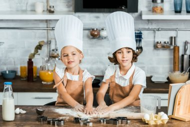 adorable children in aprons and chef hats preparing dough for tasty cookies together