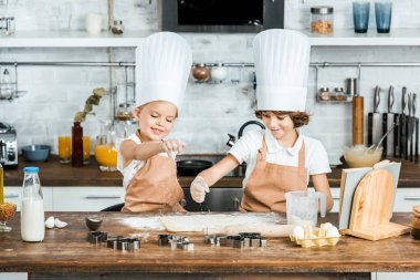 cute happy children in aprons and chef hats preparing dough for tasty cookies together