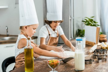 cute little kids in aprons and chef hats preparing dough for tasty cookies together