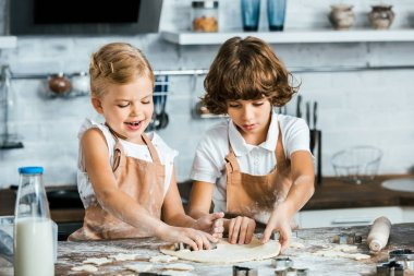 adorable smiling children in aprons preparing dough for tasty cookies