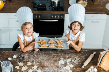 high angle view of happy kids in chef hats holding baking tray with ginger cookies and smiling at camera