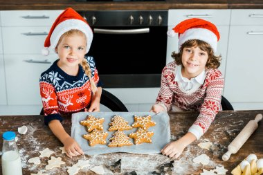 high angle view of adorable happy children in santa hats holding baking tray with ginger cookies and smiling at camera