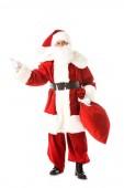 Santa claus drží pytel a ukazující daleko při pohledu na fotoaparát izolované na bílém
