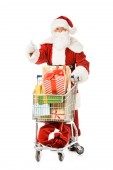 Photo santa claus with shopping cart full of gift boxes showing thumb up isolated on white