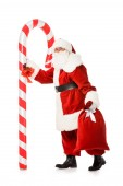 santa claus with giant candy cane and sack walking isolated on white