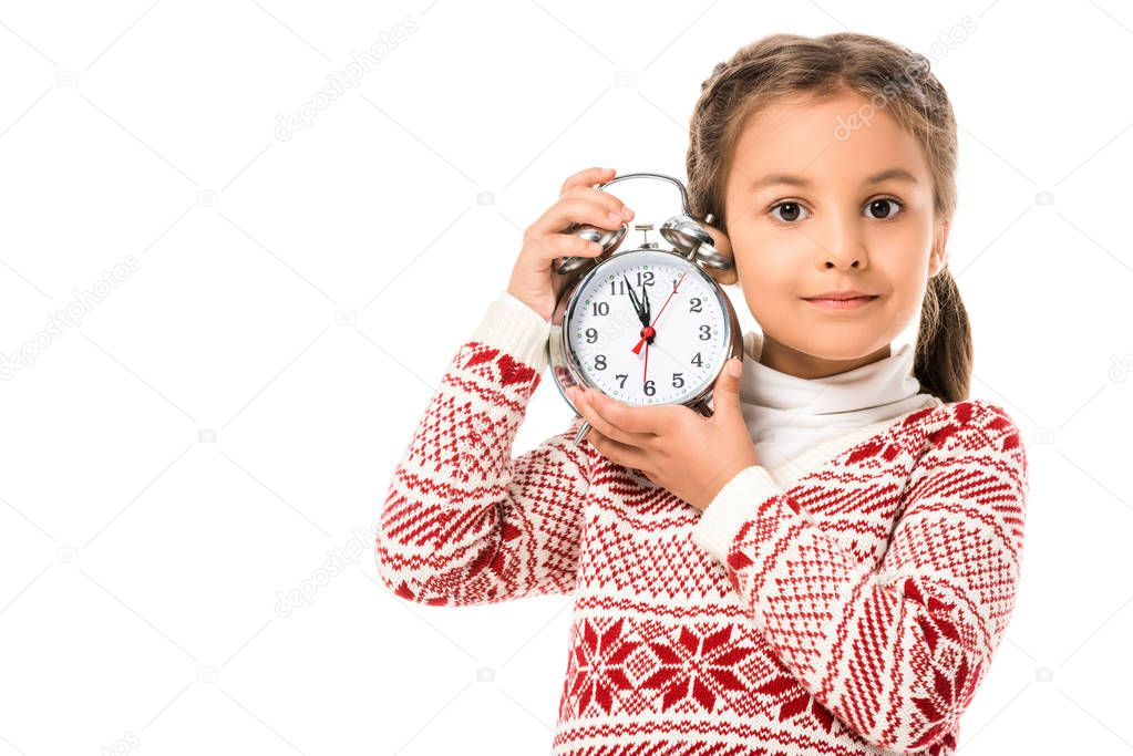 adorable little child holding alarm clock and looking at camera isolated on white