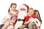 gyerekek és a santaembracing és a kamera nézett, miközben ül a karosszékben együtt elszigetelt fehér