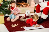 Fotografie cropped shot of kids unpacking gifts and drawing on floor in front of santa