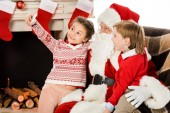 Fotografie happy kids taking selfie with santa while sitting in armchair together