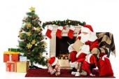 happy kids and santa relaxing in front of fireplace isolated on white