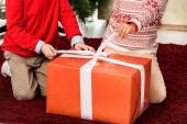 oříznutý snímek děti otevření červené vánoční dárek