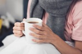 Fotografie cropped shot of sick woman in bed holding cup of hot tea