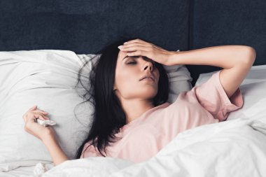 sick young woman with high temperature lying in bed