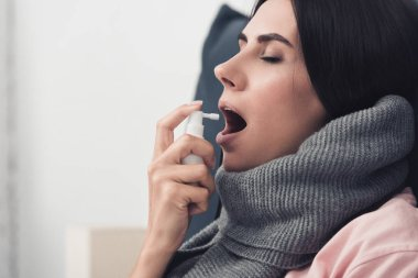 sick young woman in scarf using cough spray