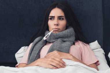 sick young woman measuring temperature with mouth thermometer while lying in bed