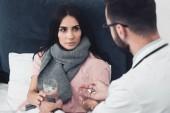Fotografie Arzt, Patientin Wasser und Pillen geben und im Bett liegend