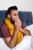 Fotografie sick young man sneezing while lying in bed