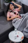 Fotografie pohled z vysokého úhlu nemocné mladé ženy s vysokou teplotou podržíte ledový obklad na hlavu a ležet na gauči